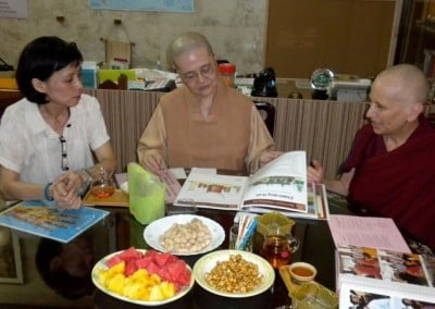 Venerable Chodron talking to a Chinese nun who is looking at Sravasti Abbey photos.