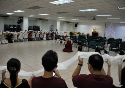 A group of people kneeling down in a circle and holding a long khata, Venerable Chodron kneeling down in the centre.