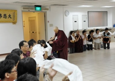Women and men kneeling down and offering the long khata to Venerable Chodron.