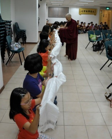 Children, women and men kneeling down and offering the long khata to Venerable Chodron.