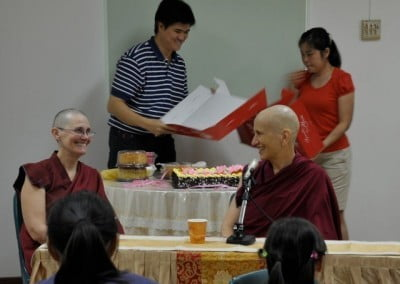 Venerable Chodron and Venerable Choyi smiling happily to each other, while some volunteers put a cake on the table behind them.