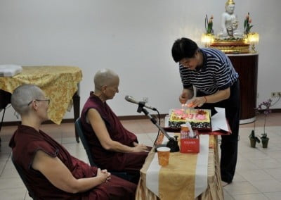 A man lighting the candles on the cake with Venerable Chodron and Venerable Choyi looking on.