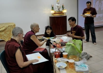 A man and a woman making an offering to Venerable Chodron.