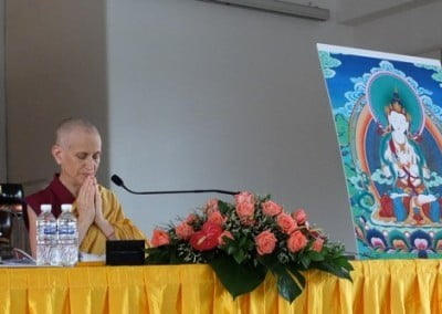 Venerable Chodron closing her eyes and hands praying, beside her is a large image of Vajrasattva.
