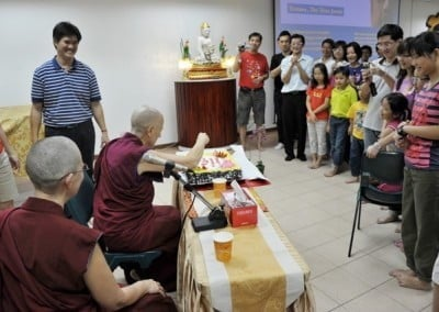 Venerable Chodron cutting the cake with everyone looking with happy smiles on their faces.