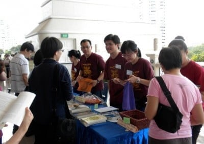 Volunteers from Friends Of Sravasti Abbey Singapore standing behind a long table talking to members of the public.