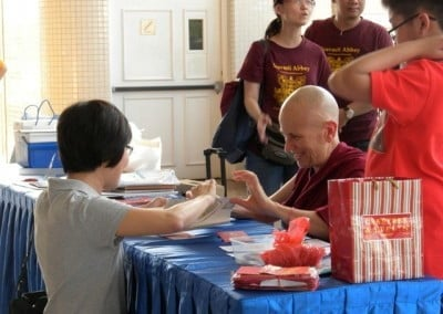 Venerable Chodron signing a book for a woman who is kneeling down.
