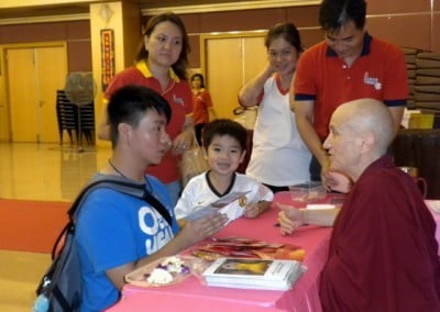 A youth kneeling down and talking to Venerable Chodron, a young boy and some volunteers looking at Venerable Chodron.