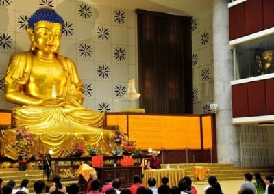 Venerable Chodron giving a dharma talk to a large numbers of people in a big hall, behind her is a huge statue of Medicine Buddha.