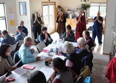 Buddhist nuns, anagarika and retreatants chanting prayers at the dining table before lunch.