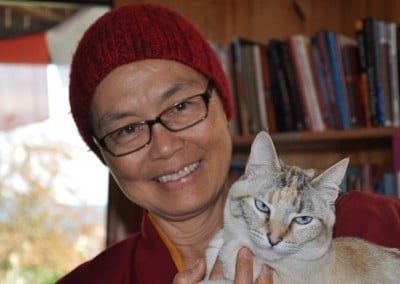 A close up photo of Buddhist nun, Venerable Tenzin Kacho smiling happily with Abbey cat, Karuna.