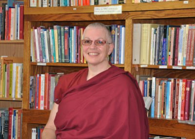 Buddhist nun, Venerable Yeshe smiling happily. Behind her are bookshelves filled with books.