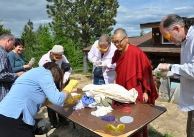Buddhist nun, Venerable Kacho with four retreatants wearing big latex gloves and glasses with yellow cellophane, pick out colored beads from plastic container.
