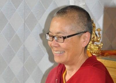 A close up photo of Buddhist nun, Venerable Tenzin Kacho smiling happily.