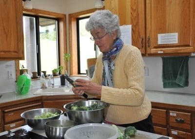 A woman cutting broccoli and putting them in steel bowls in Abbey kitchen.