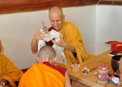 Venerable Chodron places the relic of the Buddha on Venerable Samten's head.