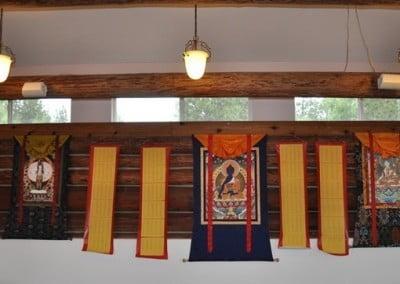 Five long list of prayer names hanging on wall of the meditation hall.