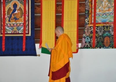 Buddhist nun, Venerable Samten checking a piece of paper against two long list of names (hanging on the wall) who had requested prayers from Singapore.