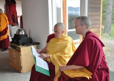 Buddhist nuns, Venerables Jigme and Tarpa sitting side by side reviewing papers inside a file.