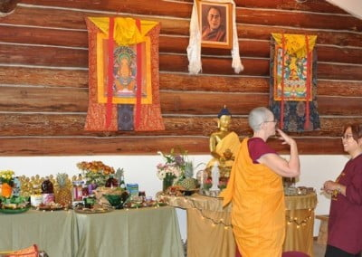 Buddhist nun, Venerable Chonyi talking to a woman in front of the Buddha altar.