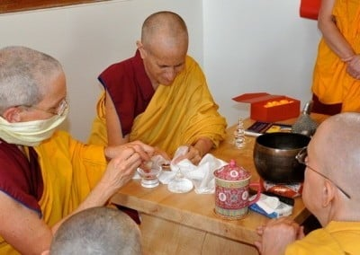 Buddhist nun, Venerable Semkye gently prepares to transfer a rare and precious relic of the Buddha to its new home.