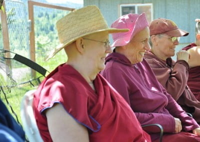 Buddhist nun, Venerable Chodron, Venerable Jigme and Venerable Semkye sitting in a row, smiling happily.