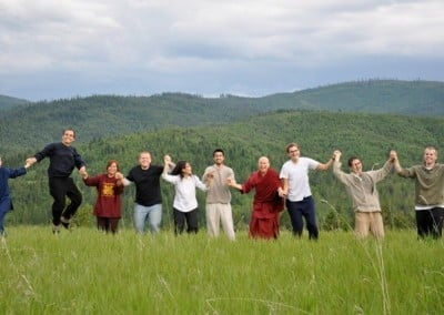 Venerable Chodron and young adults holding hands and standing in a row in the open field.