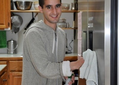 A youth using a white cloth to clean the fridge in the kitchen.