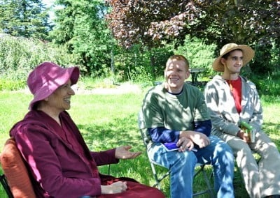 Venerable Chodron sitting on chairs in the open field with two youths.