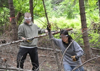Two youths wearing goggles taking long branches from the forest.
