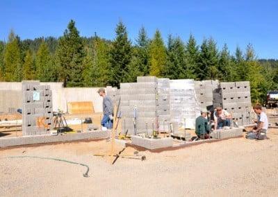 Three men squatting and looking at a faswall building block, stacks of Faswall behind them.
