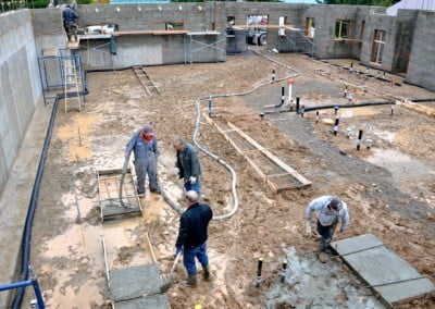 Workers working at the muddy construction site.