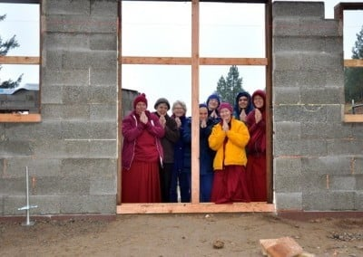 Abbey sangha, anagarikas and lay people posing at the large door with only wooden planks.