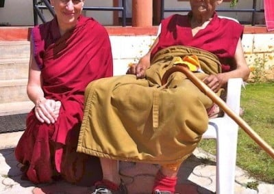 Buddhist nun Venerable Chodron squatting beside a buddhist monk who is sitting on a chair.