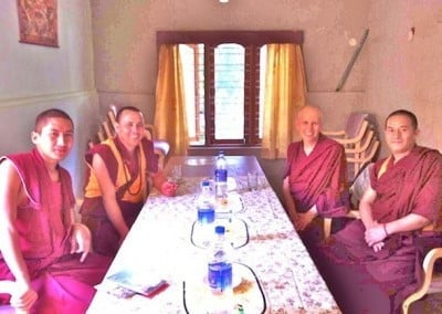 Buddhist nun Venerable Chodron sitting at the table with three buddhist monks.