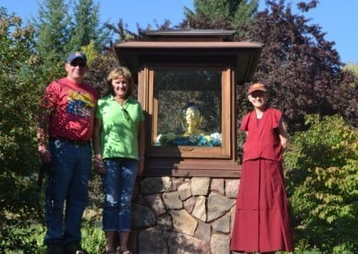 Ven. Samten and her sister, Cheryl, and husband, Paul, pose with the Buddha.