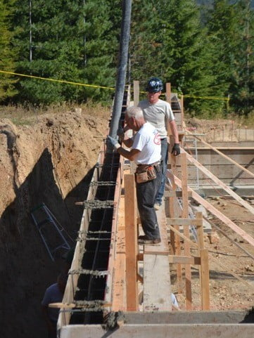 A man holding the long tube from which the concrete will flow to fill the blocks
