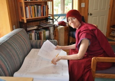 Buddhist nun, Tarpa sitting on a chair looking at the floor plan, a large floor plan is placed on the sofa.