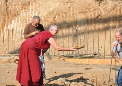 Buddhist nun, Venerable Yeshe bending her body to offer a plate of cookies to some men.