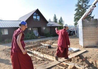 Vens. Chodron and Tarpa cross the plank onto the building site.