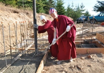 Buddhist nun, Venerable Chodron holding a pole while Venerable Tarpa is holding a spade.