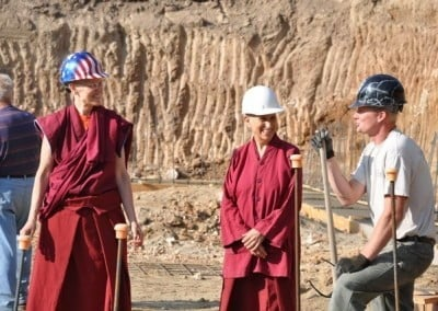 A man talking to buddhist nuns, Venerable Chodron and Venerable Tarpa at the site.