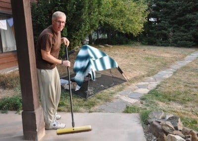 A man sweeping the patio.