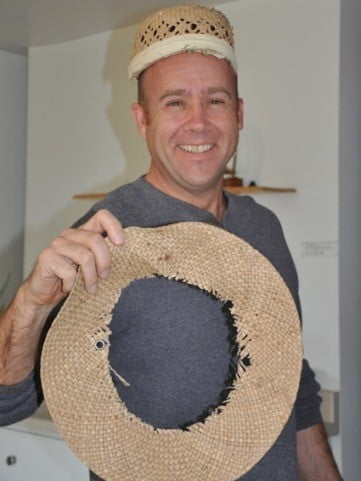 A man wearing a straw hat and holding the brim that has been removed from it