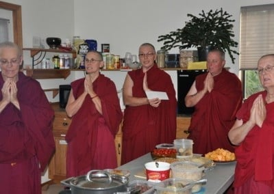 Abbey sangha standing around a table of food, praying.