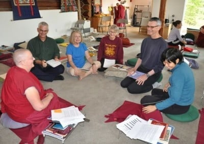 Three women, two men and a buddhist nun sitting in a circle on the floor.
