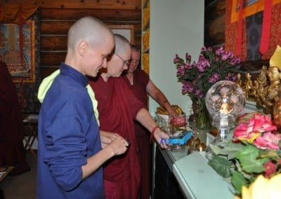 Two buddhist nuns and one anagarika standing and looking at the Buddha altar.