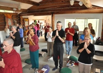 Retreatants standing with their hands in praying gestures.