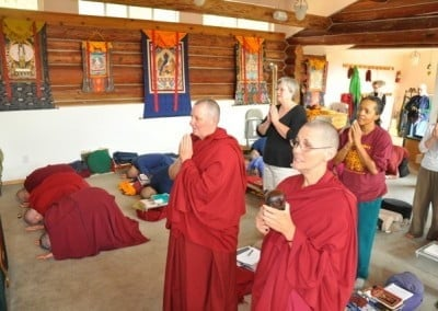 One group of retreatants and sangha on the right side bowing down on the floor, the other group on the left side chanting and hands in praying gestures.