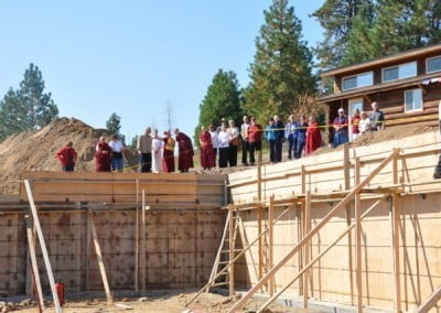 Abbey sangha and retreatants looking at the foundation of the Chenrezig hall from above
